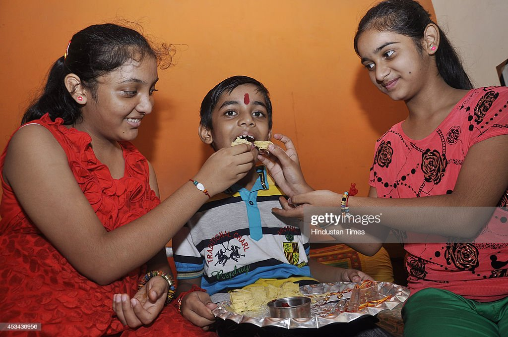 Children celebrating the festival of 'Raksha Bandhan' at Lohiya Nagar on August 10, 2014 in Ghaziabad, India. The festival of Raksha Bandhan' or 'Rakhi' celebrate the brother-sister love. Sisters tie sacred Rakhi string on their brothers' right wrists and pray for their protection.