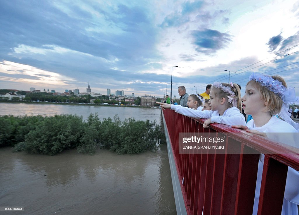 Children celebrating their first communion watch from a bridge high water at Wisla river in Warsaw on May 20, 2010. Flash floods caused by days of heavy rainfall have hit parts of central Europe, killing at least seven people, disrupting power supplies and forcing thousands of people from their homes. Southern Poland, parts of the Czech Republic and Slovakia and northern Hungary are among the worst affected regions