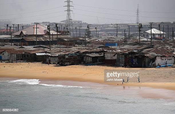 Children chase a soccer ball along the beach of the West Point slum on February 10 2016 in Monrovia Liberia West Point the most impoverished and...