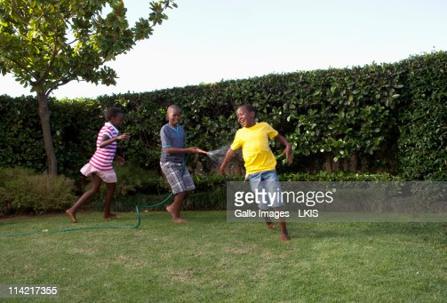 Children chasing each other with water hose, Johannesburg, South Africa