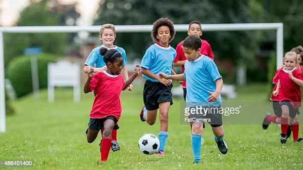 Kinder verfolgen einen Fußball bei einem Spiel