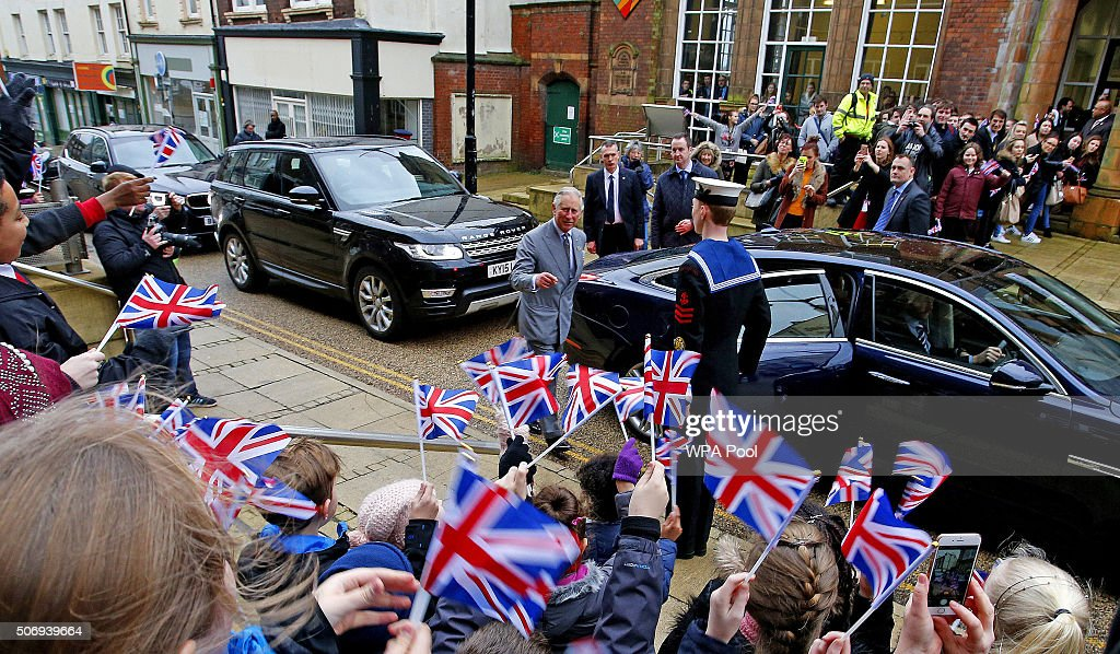Children cheer and wave flags for Prince Charles Prince of Wales Patron and Founder of the Prince's Regeneration Trust following his visit to the...