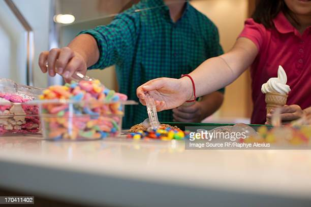 Children choosing toppings in store