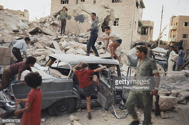 Children clamber on and play in a wrecked car on a bomb site in Amman Jordan following a period of fighting between Jordanian Armed Forces and the...
