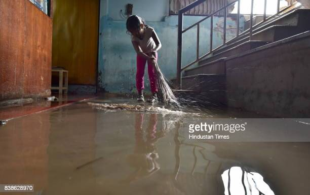 Children cleaning a doctor's clinic after the water receded in Rammurthy Nagar on August 24 2017 in Bengaluru India The area was flooded after last...