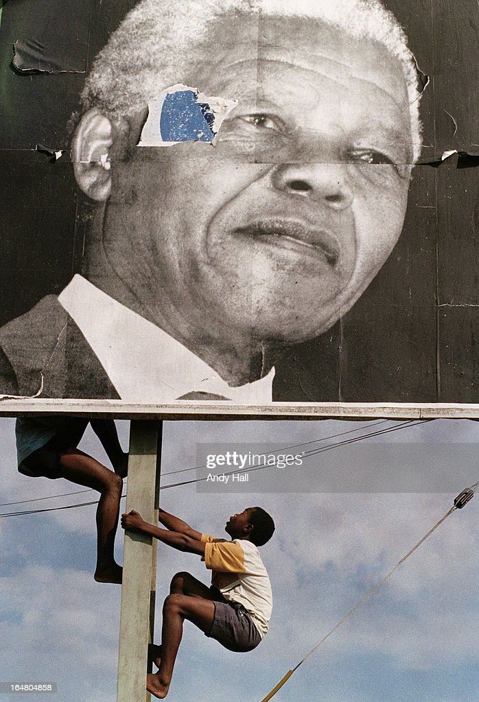 Children climb a massive billboard of ANC leader Nelson Mandela as they come out to greet him during South Africa's first democratic elections on April 16, 1994 in Ladysmith, Kwazulu Natal, South Africa.