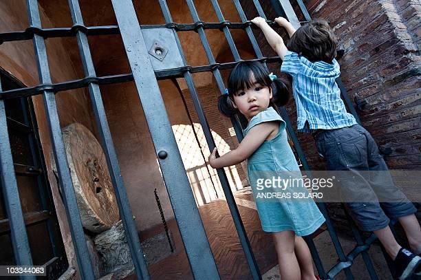 Children climb the gates of the monument Bocca della Verita in central Rome on August 11 2010 AFP PHOTO / ANDREAS SOLARO