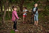 little children gather firewood. Hard work in the woods.