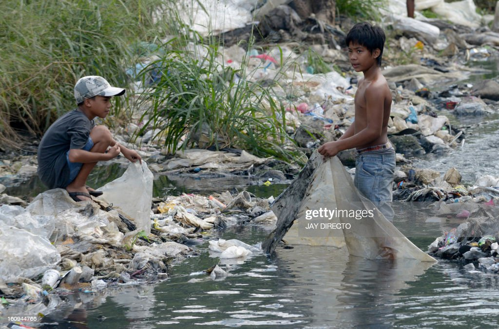 Children collect plastic to be sold and recycled at a polluted river in suburban Manila on February 8, 2013. The city's trash disposal agency traps solid waste floating down waterways that was thrown into the water by residents of slums along riverbanks upstream. AFP PHOTO / Jay DIRECTO