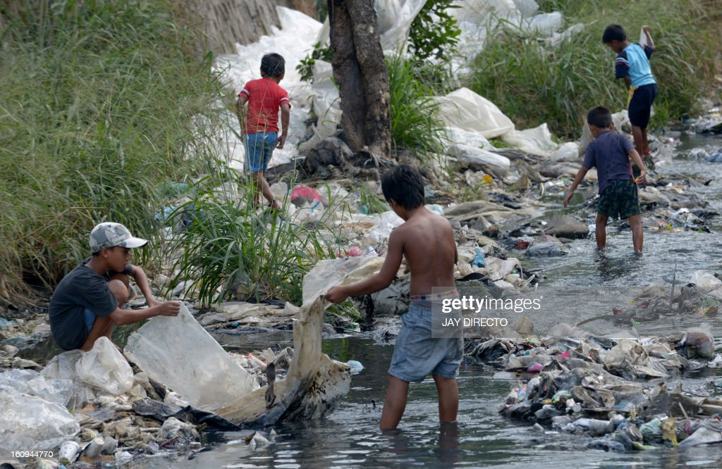 Children collect plastic to be sold and recycled, in a polluted river in suburban Manila on February 8, 2013. The city's trash disposal agency traps solid waste floating down waterways that was thrown into the water by residents of slums along riverbanks upstream. AFP PHOTO / Jay DIRECTO