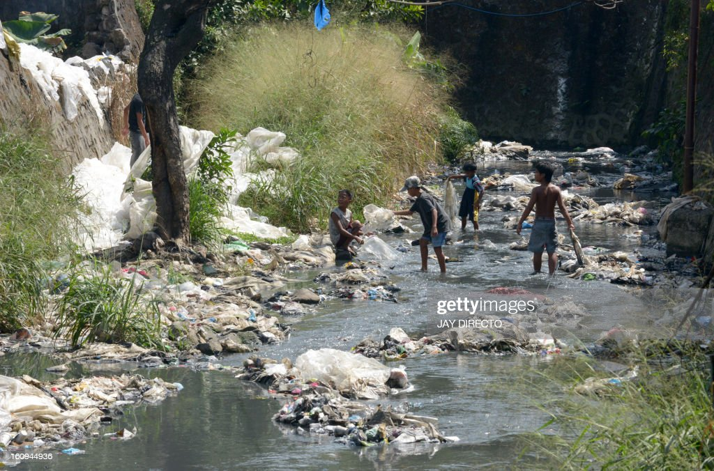 Children collect plastic to be sold and recycled, on a polluted river in suburban Manila on February 8, 2013. The city's trash disposal agency traps solid waste floating down waterways that was thrown into the water by residents of slums along riverbanks upstream. AFP PHOTO / Jay DIRECTO