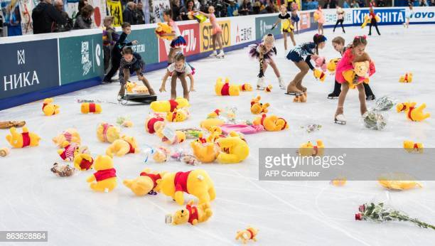 Children collect stuffed toy bears from the ice after Japan's Yuzuru Hanyu performed his routine in the men's short program at the Rostelecom Cup...