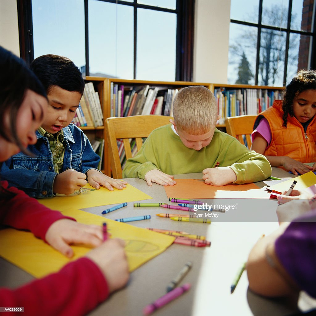 children coloring with crayons at table in classroom stock photo