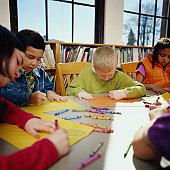 Children (8-10) coloring with crayons at table in classroom