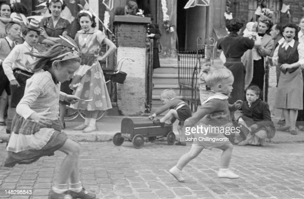 Children competing in an eggandspoon race held at a party to celebrate the coronation of Queen Elizabeth II held in Morpeth Street in London's East...