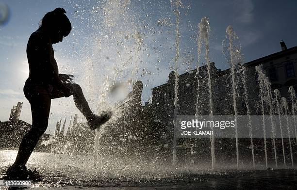 Children cool down in a fountain outside of Columbus Shopping centre in Vienna on August 11 2015 as a heat wave continues in the region where...