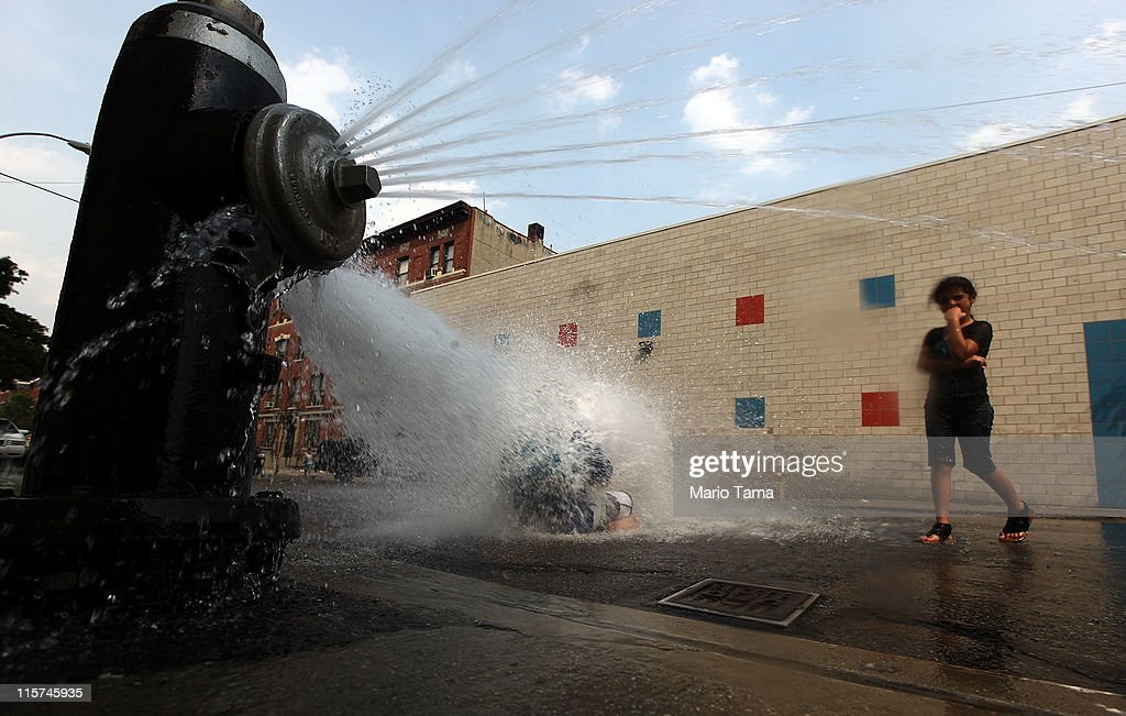 Children cool off in water sprayed from a fire hydrant on June 9, 2011 in the Bronx borough of New York City. An early summer heat wave has hit the city with temperatures forecast to hit in the high nineties this afternoon.