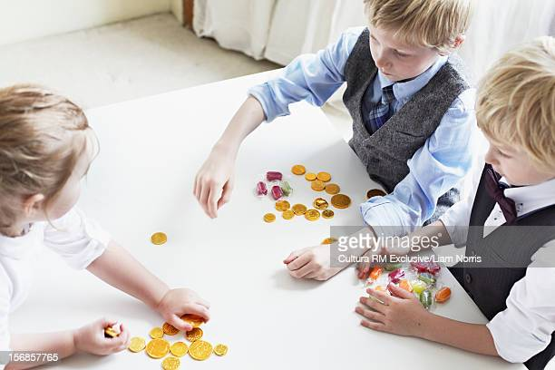 Children counting coins and candy