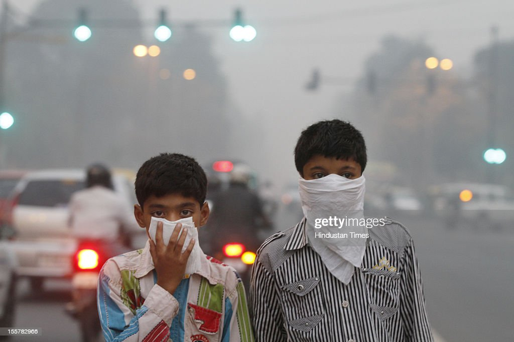 Children cover their face to take precaution from the air pollution by a mixture of pollution and fog at NCR region on November 7, 2012 in New Delhi, India.