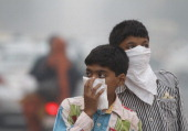 Children cover their face to take precaution from the air pollution by a mixture of pollution and fog at NCR region on November 7 2012 in New Delhi...