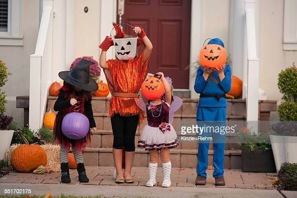 Children covering face with Jack O Lantern bucket in front of house