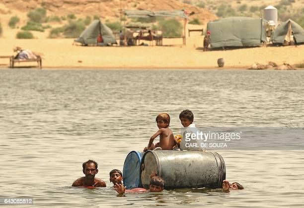 Children cross a flooded area on empty oil drums near an army run relief camp in Sehwan Sindh province Pakistan on September 16 2010 Antonio Guterres...