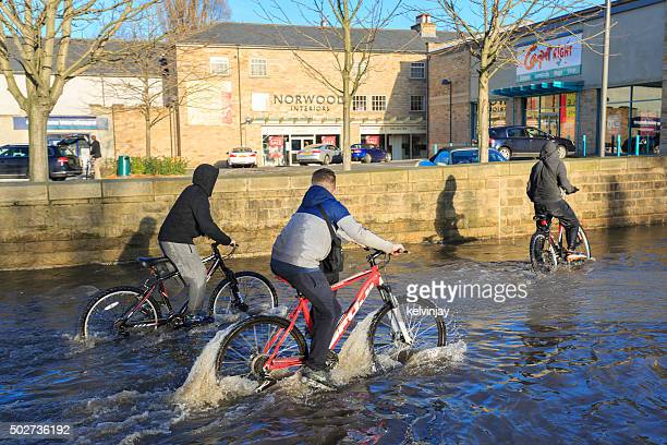 Children cycling on a flooded street past shops in Leeds