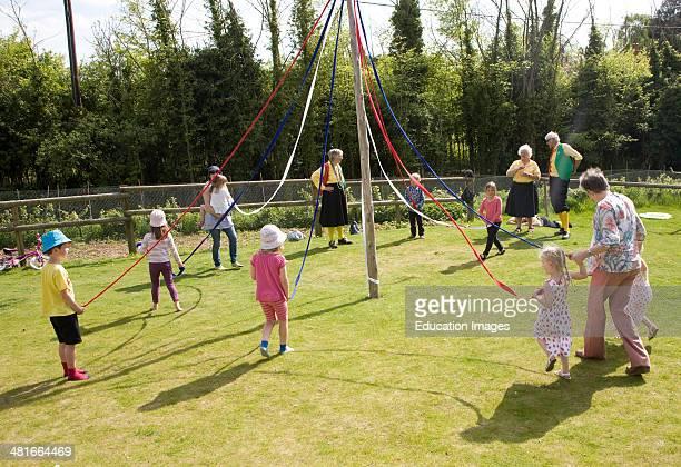 Children dance around a maypole at an English country festival Shottisham Suffolk England