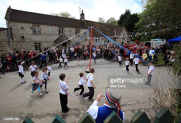Children dance around the maypole as outside the village pub and hall at the May Day village celebrations in Priston on May 7 2012 in Somerset...
