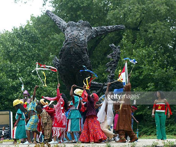 Children dance around the National Monument for Slave Trade History after its unveiling July 1 2002 in Amsterdam Netherlands The monument honors...
