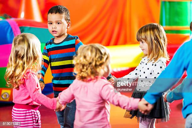 Children dancing in a playroom.