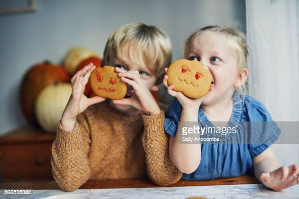 Children decorating pumpkin shaped biscuits together