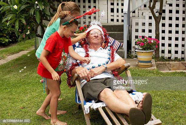Children (7-9) decorating senior man with Christmas decorations in yard