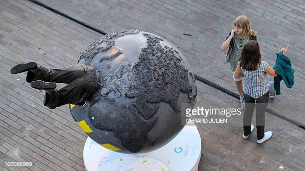 Children discover a giant model globe part of an art installation entitled 'Cool Globes' against global warming and climate change in Marseille...