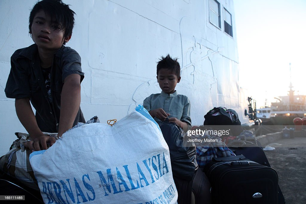 Children displaced by continuing armed conflict between the supporters of Philippine Muslim clan Sulu Sultan Jamalul Kiram III and Royal Malaysian Police in Sabah, Malaysia, arrive at Bonggao Port on March 30, 2013 in Bonggao, Tawi-Tawi, Philippines. Following the insurgency in Sabah and the Malaysian government's subsequent crackdown on undocumented Filipinos, over 4000 people, mostly Filipino Muslims, have begun evacuating to the southern provinces of Basilan, Sulu, and Tawi-Tawi in the Philippines, with numbers expected to reach more than 100,000.