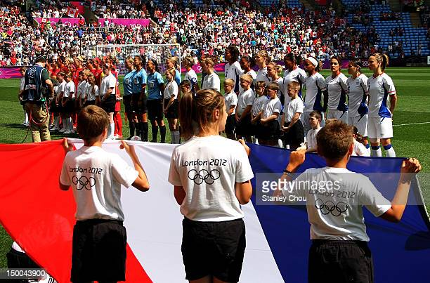 Children displays the national flag of France foregrounds France and Canada during the national anthem during the Women's Football Bronze Medal match...