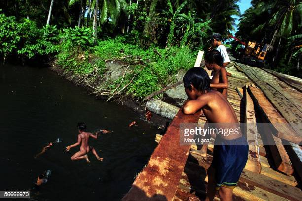 Children dive off the newly constructed coconut lumber Liangan Bridge a project initiated by the traditional village leaders and was later on...