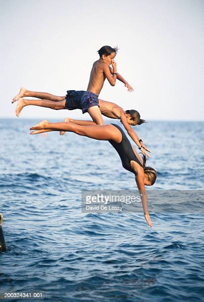 Children (8-17) diving into sea, side view