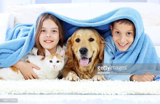 Children, dog and cat looking out the blanket.