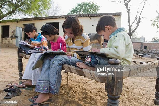 Children doing homework on a cot, Hasanpur, Haryana, India