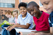 Multiethnic children sitting in a row and reading from notebook all together. School kid revising notes for exams sitting on the steps outside the elementary school. Latin school boy studying with fri