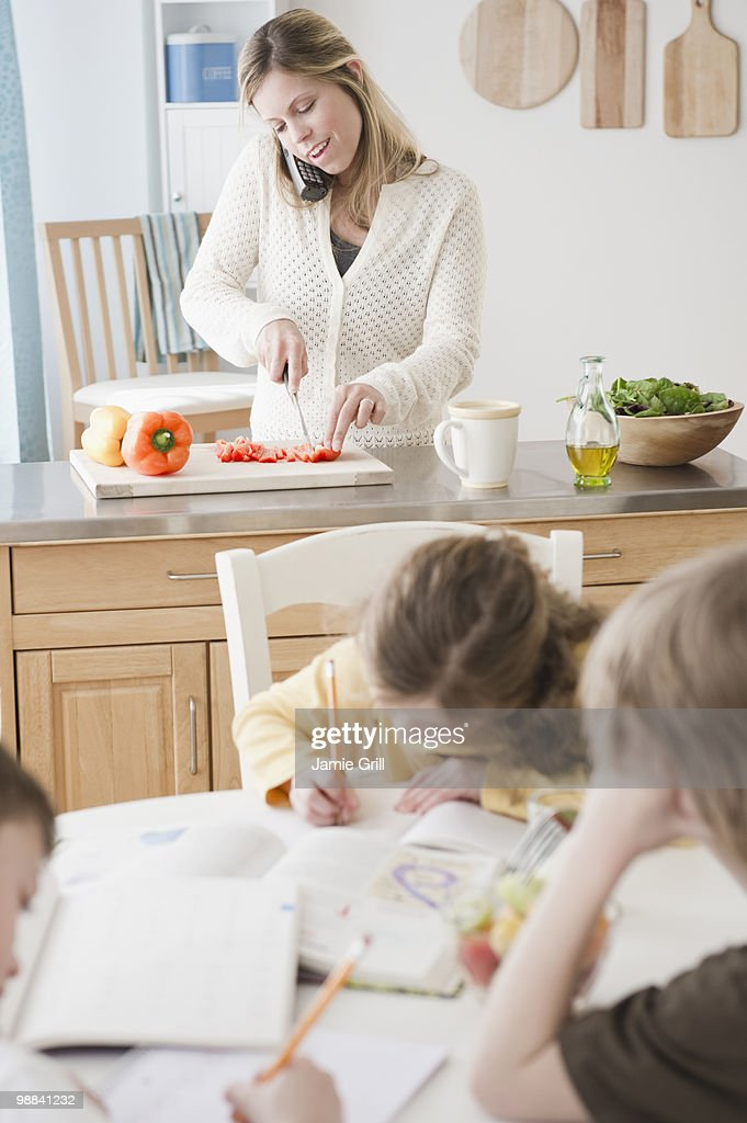 Children doing homework while their mother cooks : Stock Photo