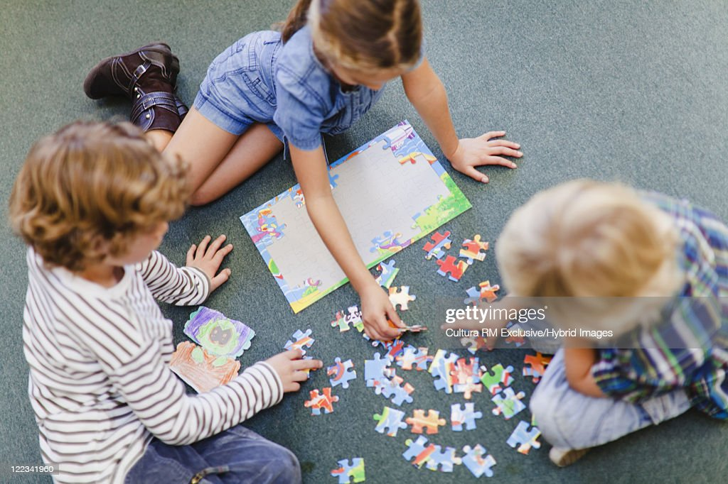 Children doing puzzle together : Stock Photo