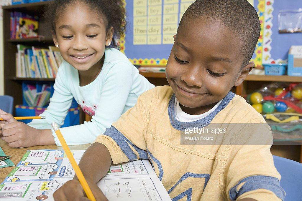 Children doing school work in classroom : Stock Photo