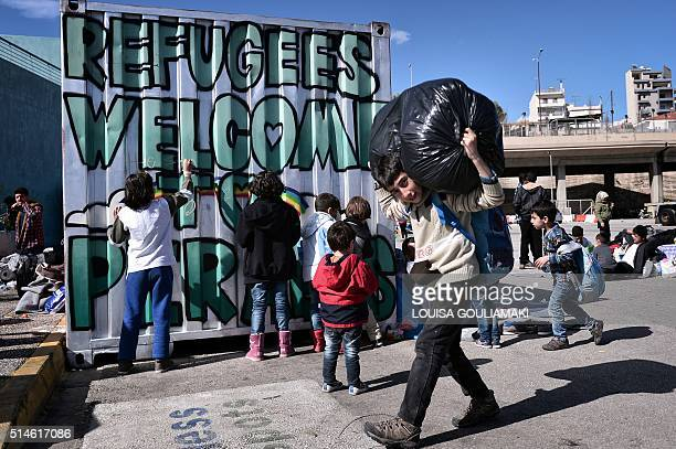 Children draw on a container in the port of Piraeus on March 10 as they wait with other migrants and refugees to be transferred to refugee camps in...