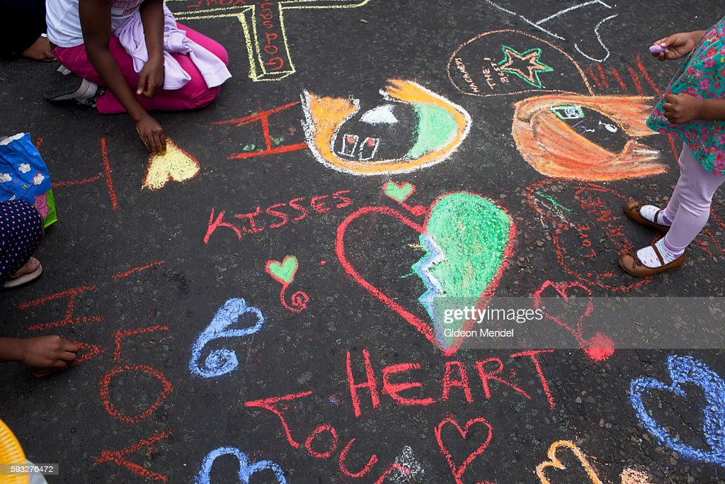 Children draw positive messages on a street which a week earlier had seen violent clashes between local youth and police This scene was at a...
