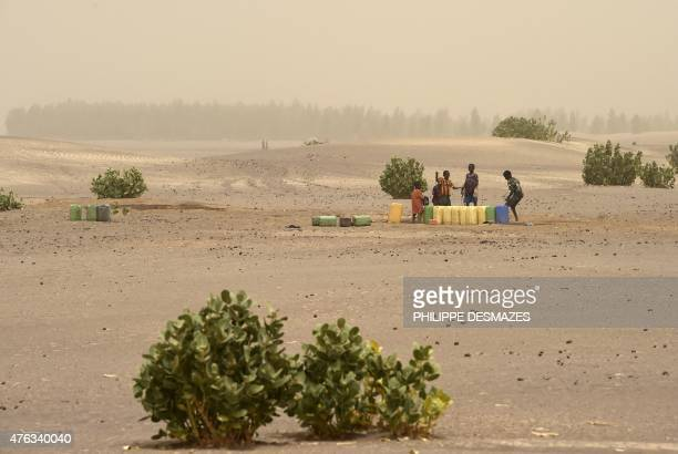 Children draw water from a well on June 4 2015 on the dry lake of Faguibine near Bintagoungou in the region of Timbuktu northern Mali while French...