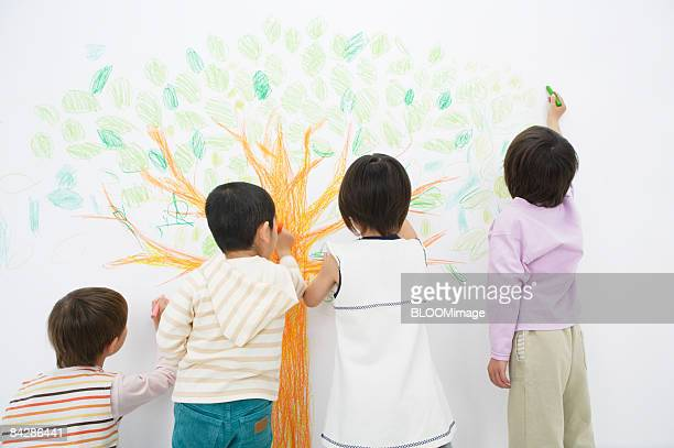 Children drawing a tree, rear view