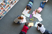 Elementary children lying on the floor and drawing at library. Top view of five multiethnic boys and girls in daycare house drawing on copybook. High angle view of group of kids drawing with colorful