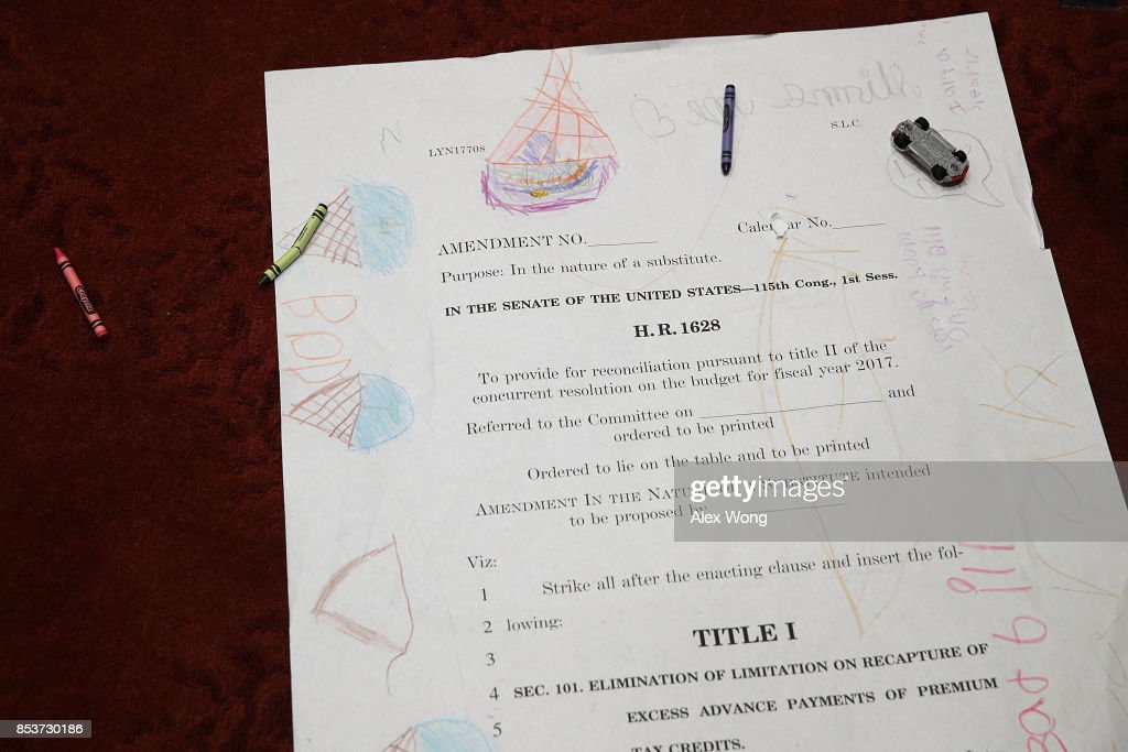 Children drawings are seen on an enlarged page one of the American Health Care Act of 2017 during a news conference on health care September 25, 2017 on Capitol Hill in Washington, DC. Activists gathered to urge to reject the Graham-Cassidy health care bill.